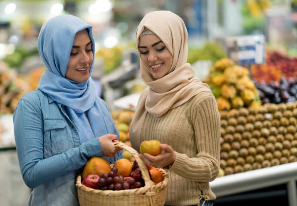 Two women select fruit in a super market