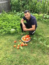 ISA employee Arben with garden vegetables